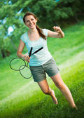 Smiling girl with a racket for a badminton in the park — Stock Photo