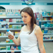 Stock Photo: Young womshopping in store household chemicals and cosmet