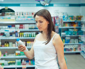 Young woman shopping in the store household chemicals and cosmet — Stock Photo