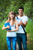 Two students studying in park with book outdoors — Stock Photo