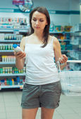 Young woman shopping in the store household chemicals and cosmet — Photo