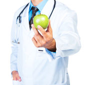 Doctor's hand holding a fresh green apple close-up on white — Stockfoto