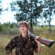 Young beautiful girl with a shotgun in an outdoo — Stock Photo