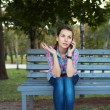 Portrait of a woman in a park on a bench talking on the phone — Stock Photo #31900633