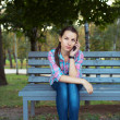 Portrait of a woman in a park on a bench talking on the phone — Stock Photo #31900643