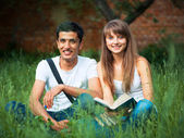 Two students in park on grass with book outdoors — Stock Photo