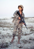 Weibliche soldat gekleidet in eine tarnung mit einer waffe im freien — Stockfoto