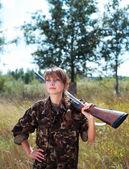 Young beautiful girl with a shotgun outdoor — Stock Photo
