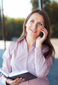 Businesswoman with cellphone and organizer — Stock Photo