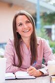 Kobieta siedzi w kawiarni w notatniku — Zdjęcie stockowe