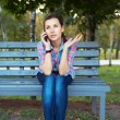 Portrait of a young woman in a park talking on the phone — Stock Photo #33377239