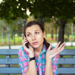 Portrait of a young woman in a park talking on the phone — Stock Photo #33377251