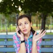 Stock Photo: Portrait of a young woman in a park talking on the phone