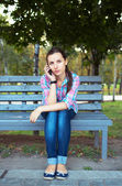 Portrait of a young woman in a park talking on the phone — Stock Photo