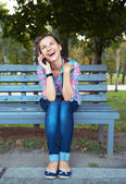 A portrait of a smiling woman in a park on a bench talking on th — Stockfoto