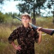 Stock Photo: Young girl with shotgun looks into distance in outdoor