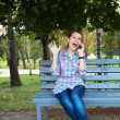 A portrait of a smiling woman in a park on a bench talking on th — Stock Photo