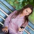 Businesswoman with cellphone and laptop in the park — Stock Photo