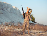 Young female soldier dressed in a camouflage with a gun in the l — Stock Photo
