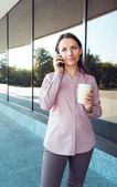 Businesswoman with cellphone and coffee while standing against o — Foto de Stock
