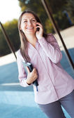 Businesswoman with cellphone and organizer while standing agains — Foto de Stock