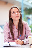 Businesswoman sitting in a cafe and writing in notepad or organi — Stock Photo