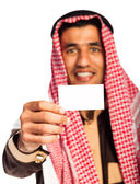 Young smiling arab showing business card in hand isolated on whi — Stock Photo