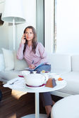 Szczęśliwa kobieta rozmawia przez telefon w kawiarni — Zdjęcie stockowe
