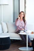 Happy businesswoman talking on the phone in a coffee shop — Stock Photo