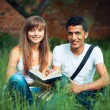 Two students guy and girl studying in park on grass with book — Stock Photo