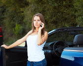 Caucasian girl on a cell phone service or tow truck traffic near — Stock Photo
