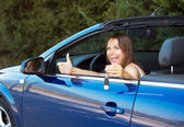 Smiling caucasian woman showing key in a cabriolet — Stock Photo