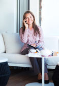 Businesswoman talking on the cellphone and writing in organizer — Stock Photo