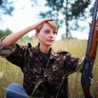 Young beautiful girl with a shotgun looks into the distance — Stok fotoğraf
