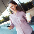 Young businesswoman with cellphone and coffee while standing aga — ストック写真