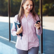 Young businesswoman with cellphone and organizer while standing — Stok fotoğraf