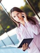 Joven empresaria con teléfono móvil y organizador estando — Foto de Stock