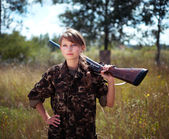 Young beautiful girl with a shotgun looks into the distance — Photo