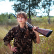 Stock Photo: Young beautiful girl with shotgun looks into distance