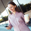 Young businesswoman with cellphone and coffee while standing aga — Foto de Stock