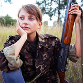 Young beautiful girl with a shotgun — Stock Photo