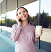 Young businesswoman with cellphone and coffee while standing aga — Stock Photo