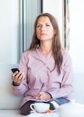 Businesswoman with cellphone in a coffee house — Stock Photo