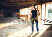 Man with a chainsaw on the ruins — Stock Photo