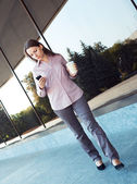 Young businesswoman with cellphone and cup of coffee outdoor — Stok fotoğraf