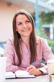 Businesswoman sitting in a cafe and writing in organizer — Stock Photo