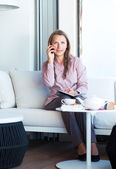 Happy businesswoman talking on the phone and writing in organize — Stock Photo