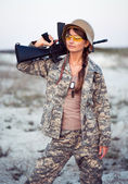 Young female soldier dressed in a camouflage with a gun in the o — Stock Photo