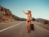 Girl on the road with a suitcase — Stock Photo