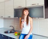 Młoda dziewczyna w kuchni, słuchanie muzyki na słuchawkach — Zdjęcie stockowe